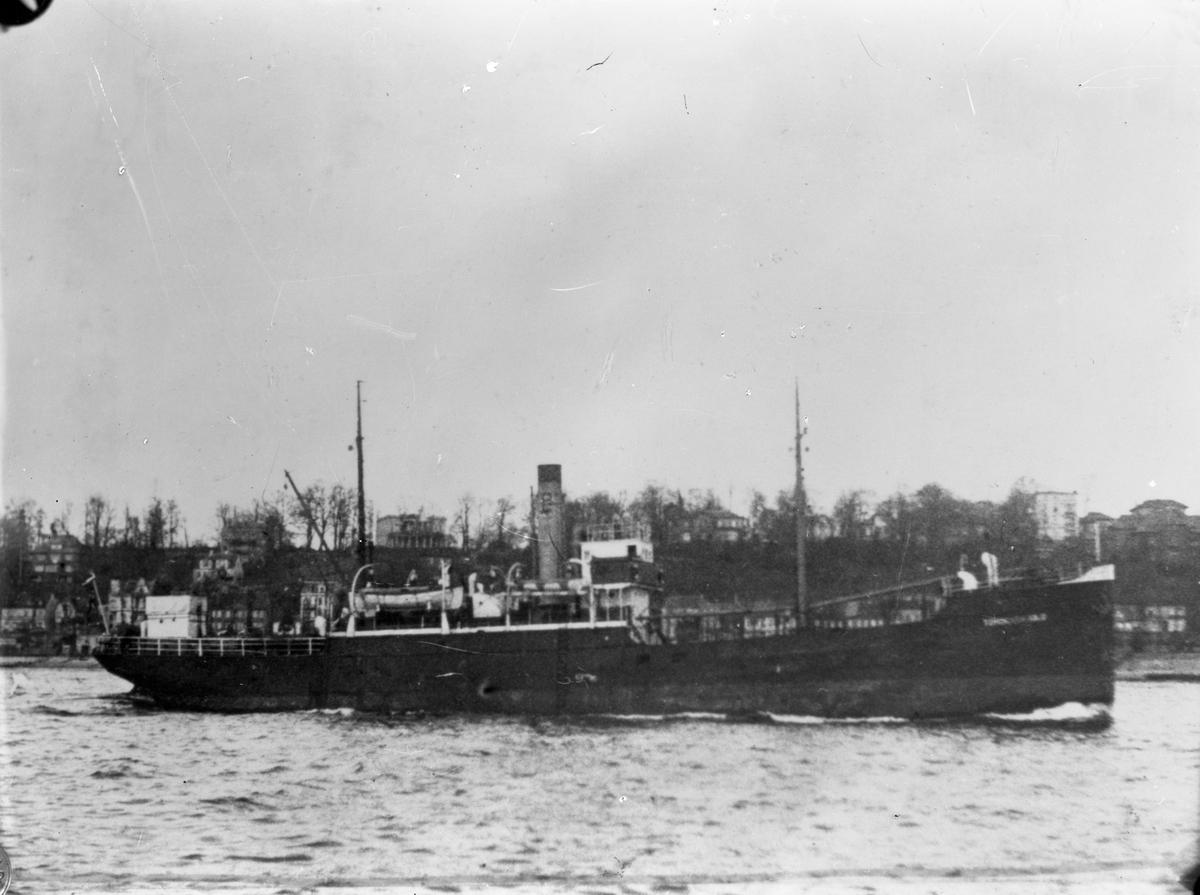 """Dampskipet D/S """"Tordenskjold"""" nær land. Flere hus i bakgrunnen, bl. a flere som ligger på en høyde."""