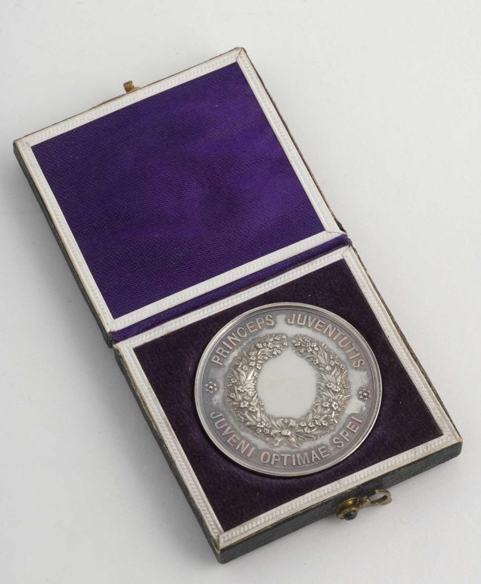 Medalje. hvitt metall. På den ene side: Oscar Gustavus  Adolphus. Norv. et Svec. Princ. Success Anno MDCCCXXII. På den annen side: Princeps Juventutis Juveni optimae spei. Sort skinnetui med fiolett fòr i fløyel og silke.