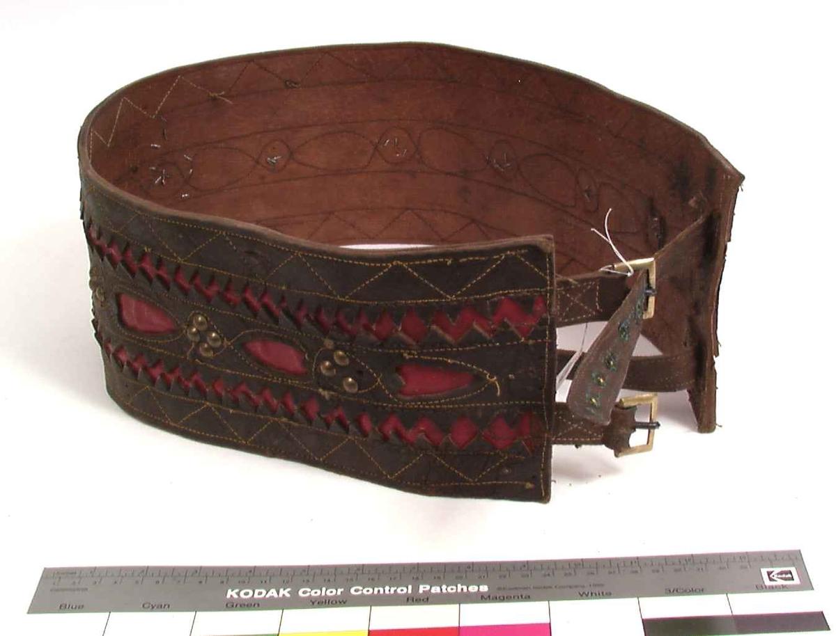 Bredt belte i rødt og brunt skinn med dekorative messingnagler og dobbel spenne.
