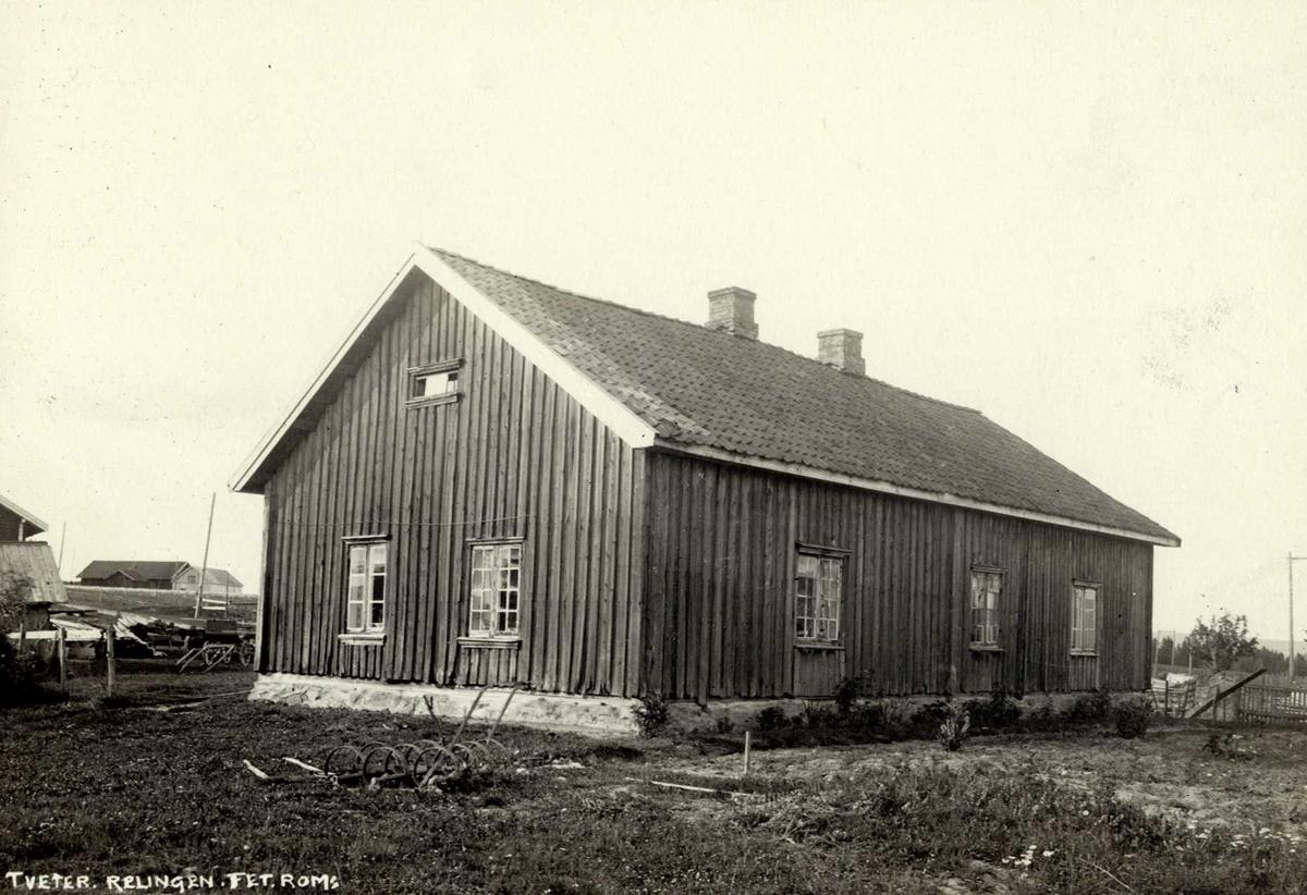 Fet, Nedre Romerike, Akershus. Grått våningshus sett fra baksiden. Jordbruksredskap for bruk av hest.