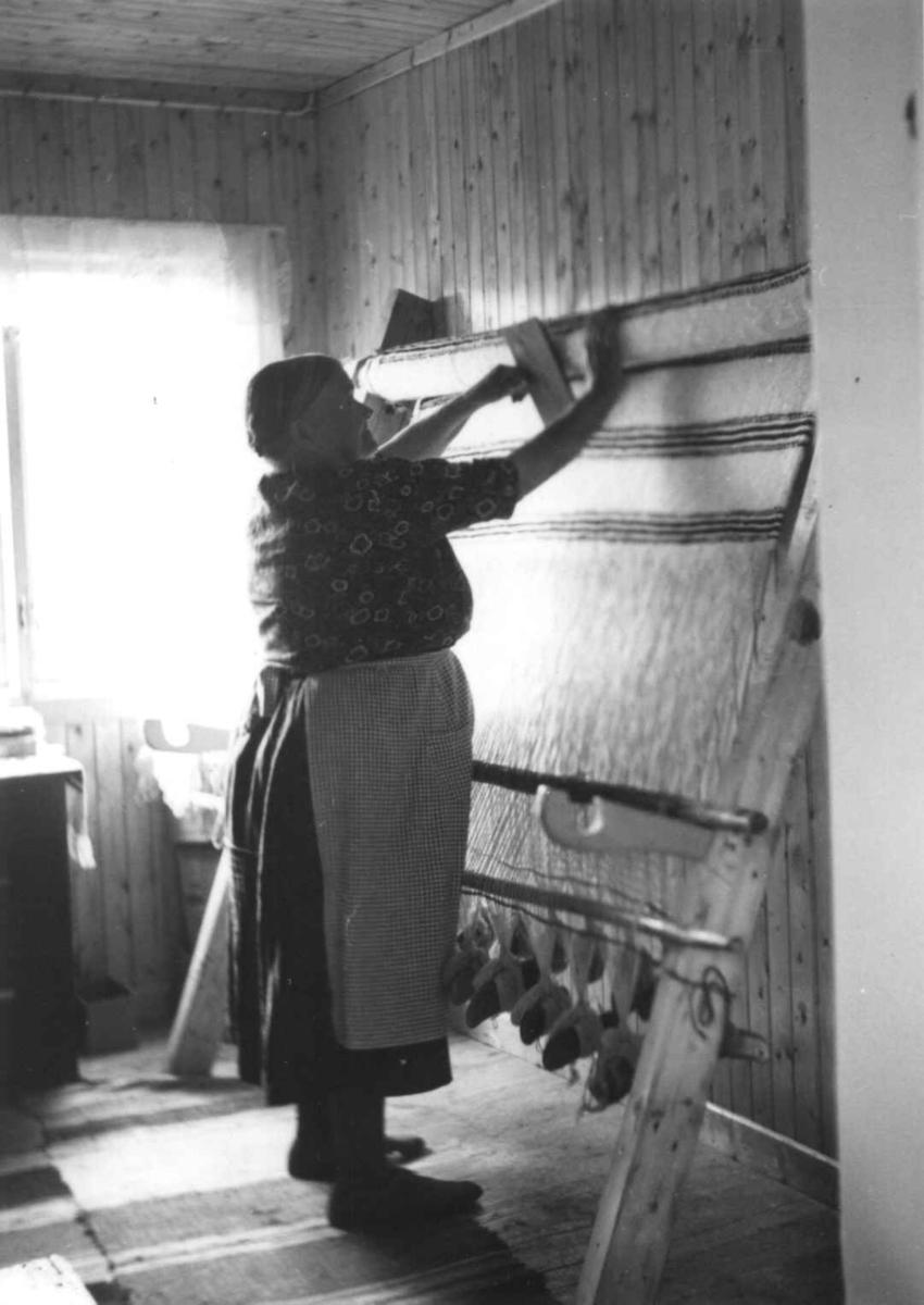 Greneveving (23). Anne Hansen karder opp greneteppet på veven. Manndalen 1955.