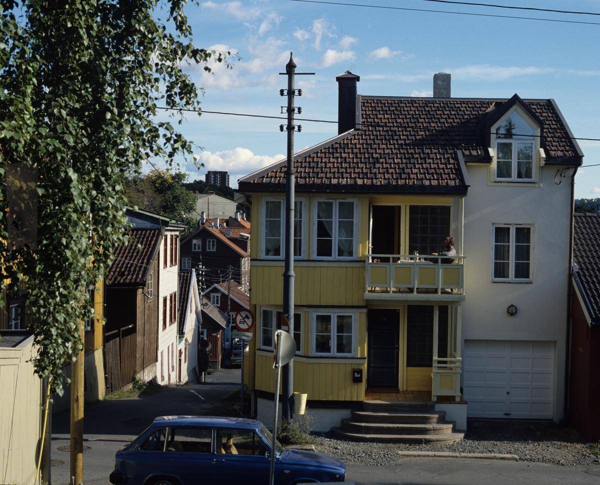 """Gatefasaden på en enebolig er delt i to, et """"murtårn"""" med garasjer litt tilbaketrukket fra trefasaden på Rodeløkka i Oslo.  Illustrasjonsbilde fra Bonytt 1986."""