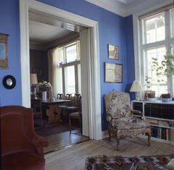 Lenestol står i  hjørne med innsyn til spisestuen med bord og stoler. llustrasjonsbilde fra Bonytt 1986.