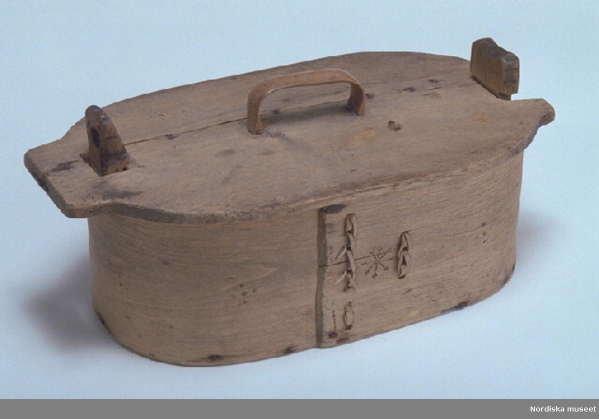 Inventering Sesam 1997-1998: L 42,5, B 22,5, H 19,5 cm Förningsask, oval, svepäska. Botten av furu, lock och svep av björk, utan fals. Svepet fästat med spikar av järn samt en dymling av trä. Hopfästning av svepet med rottågor, kedjesöm, två rader, nötta stygn. Utskurna ståndare av björk, den ena fjädrande och överkragande, fästade på svepets insida med skruvar, genomgående vid botten. Avtagbart lock, handtag av vidja fastkilat i locket, skivan spräckt och lagad med järnkrampor samt två plåtbleck på undersidan. Svep, lock, ståndarknoppar och handtag med brännstämplad dekor bl. a. punkter, stjärnor, sicksackbård. Botten ihopsatt av två brädor, fästade med dymlingar av trä. Runt hål i den fjädrande ståndaren, har funnits en lös låspinne. Agnetha Blomberg 1997