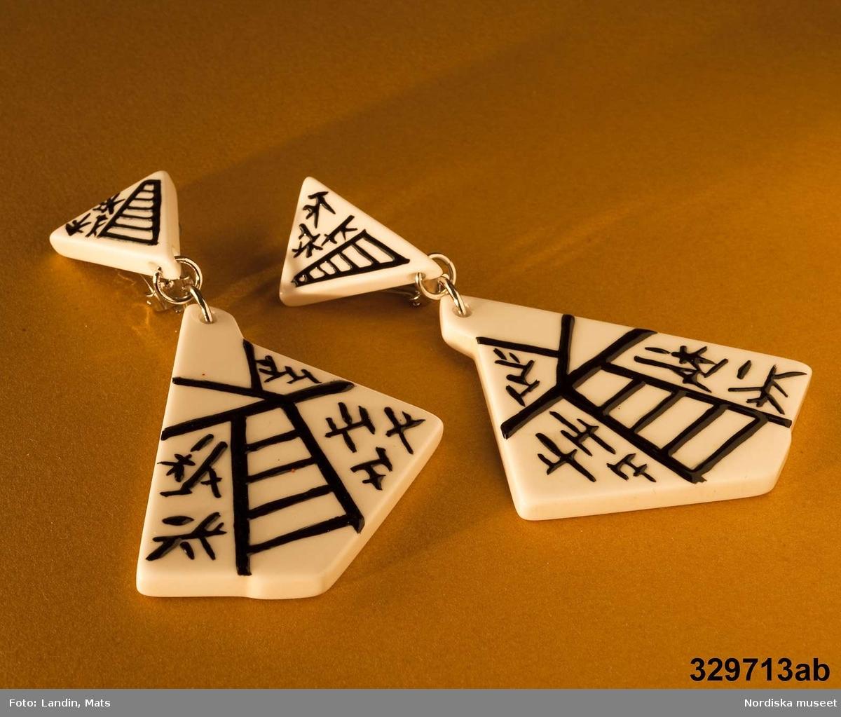Örhängen av plast, s.k. clip ons med hänge, med svarta japanska tecken på vit botten.  Klämman som sätt runt örsnibben är av metall, liksom de två ringar som håller ihop övre och undre delan av örhängena. Anm.: Ställvis något fläckiga. /Zingoalla Rosenqvist 2009-02-05