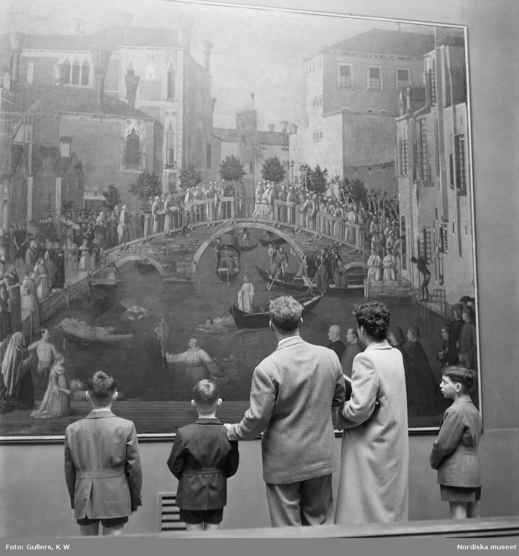 En familj med två vuxna och tre barn tittar på en målning av 1400- talsmästaren Gentile Bellinis.