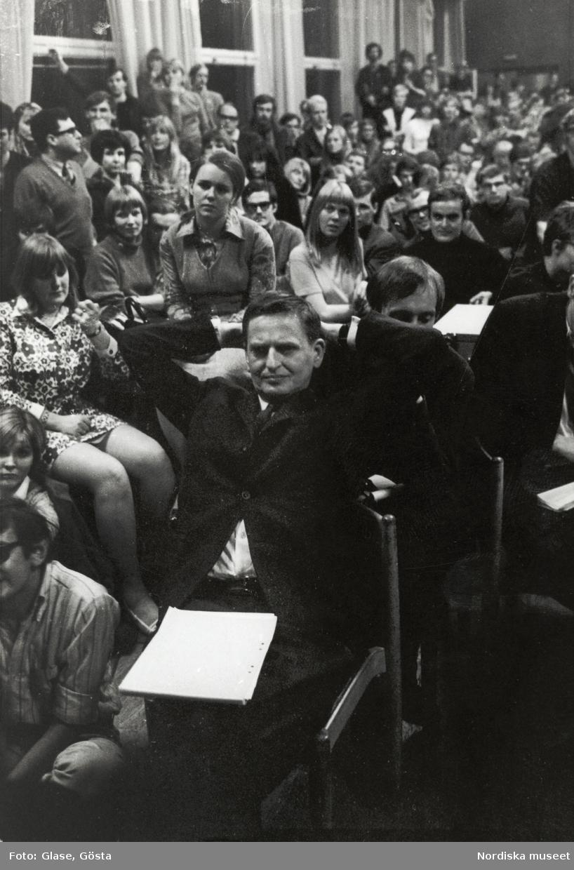 Kårhusockupationen vid Stockholms universitet i slutet av maj 1968. Bland åhörarna, i en stol, med händerna knäppta i nacken, sitter dåvarande utbildningsminister Olof Palme.