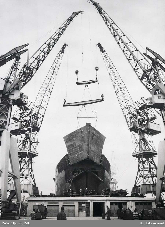 Kockums Mekaniska Verkstad i Malmö. I en docka ligger ett stort fartyg under arbete. Delarna flyttas med hjälp av lyftkranar.