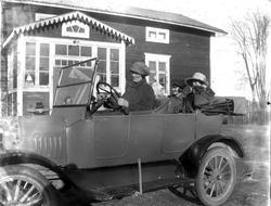 """Kvinnor och barn i en bil utanför ett bostadshus. """"T-Ford 19"""