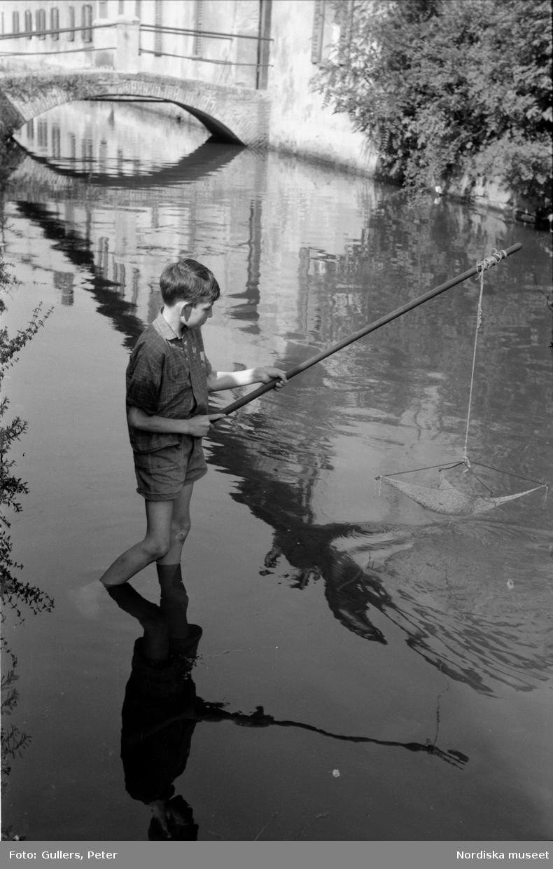 Pojke står med fötterna i vattnet i en kanal. Han håller i en håv. Italien.