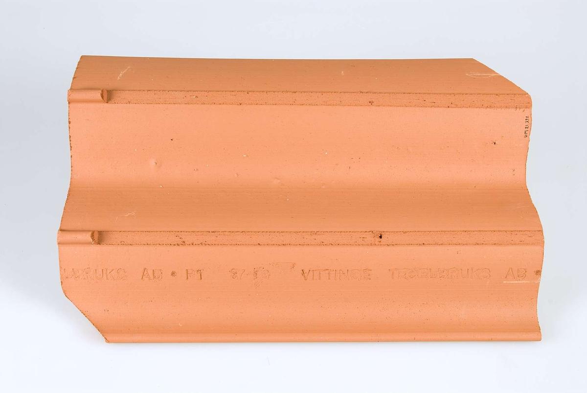Tegelrött, tvåkupigt taktegel med intryckt text på baksidan: VITTINGE TEGELBRUKS AB P1 87-03.