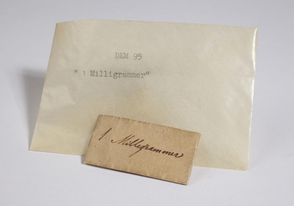 Papir brettet til en konvolutt som inneholder flere små, tynne metallbiter.
