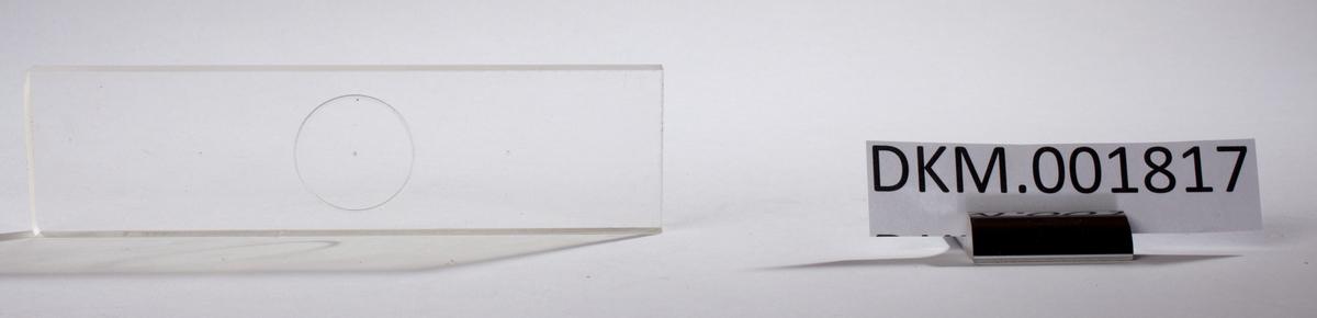 En rektangulær skive med en inngravert sirkel i midten.