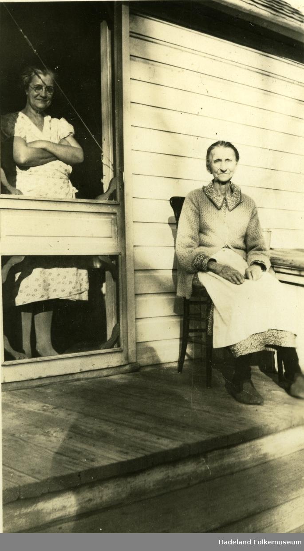 Eldre kvinne sittende ved ved inngangsdør. En kvinne står innenfor døren.