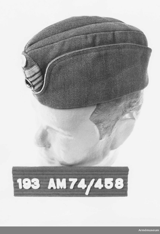 Mössan är tillverkad av gråbrungrönt ylletyg med ett yttre uppslag och en inre svettrem. Mössmärke m/1952 för överste  utgörs av på ett ellipsformat underlag utan styvnad anbringade  galoner i metallfärg och däröver en i emalj, trekronorsknapp. I  övre delen av ellipsformen finns en nationalitetsknapp i emalj. Insidan fodrad med ylletyg. En svart 6 mm bred resår är fäst  från insidan. Får lånas ut.
