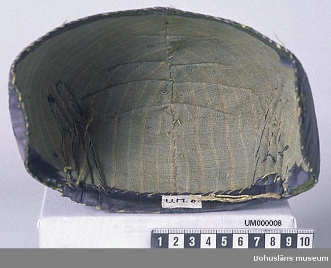 """594 Landskap BOHUSLÄN 503 Kön KVINNA  Mössan har styv stomme av papp. Yttertyg av blått siden. Fodertyg av randigt linnetyg i ljust blått, rosa och vitt (gulnat). Kantad med grönt sidenband. Broderi i tambursöm med silke i två olika kvaliteter, varav en ovanligt fin (=tunn tråd). Mönstret är ett stiliserat blommönster där en stor utsirad blomma på varje sida bildar utgångspunkt för snirkliga slingor och stjälkar, varav en del avslutas med små blommor och  knoppar. Mönstret finns över hela mössan. Färgerna i broderiet är vitt, gröntonat vitt, ljust brunrött, blått och gult. Text vid första katalogiseringen I:9:9 : """"Användes i Bohuslän långt in på 1800-talet"""". Fyra veck i varje sida bak. Vecken är svagt svängda upptill. Dragband  av grov lintråd. Mössans form är sned. Pappen skadad i sidoflikarna, de är inåtböjda i nederkanten. Sliten. Hål i yttertyget vid vecken bak och uppe på kullen. Yttertygets inslag bortslitet mitt fram, på sidoflikarnas nederkant och på många andra ställen. Sidenbandet runt nederkanten till stora delar bortslitet. Yttertyget lite och fodertyget mycket smutsigt. Svart fläck baktill på vänster sida. Blekt.  Litt; Arnö-Berg, Inga, Folkdräkter från hela Sverige, Örebro 1976, sid. 210-213.  Henschen, Ingegerd, Svenska broderier, Stockholm 1950, sid. 162-164. Nylén, Anna-Maja, Folkdräkter ur Nordiska museets samlingar, Nordiska museets handlingar 77, Lund 1971, sid. Svensson, Sigfrid, Bindmössan och dess föregångare i svensk folkdräkt ur Bygd och yttervärld, Lund 1969, sid. 36-56.  Örtendahl, Charlotte, En bindmössa från Hedemora ur Textil tradition speglad i Dalarnas museums samlingar, Dalarnas Hembygdsbok 1982, Falun 1982, sid. 45-49. Omkatalogiserat 1997-01-16 VBT  Ur handskrivna katalogen 1957-1958: Mössa; fr. Bohuslän. På styv stomme, blått siden, broderat i rött, gult, blått och vitt. Ngt blekt, luggsliten.  Lappkatalog: 77"""