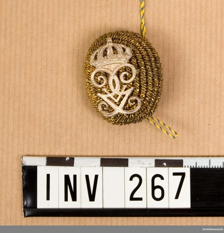 Pompong m/1865-1908, gemensam äldre modell. Rulla 1916. Av guld med H.M.Konungens namnchiffer i silver. Fästes i huvudbonaden med särskild hållare eller med plym förenad sådan. Pompongen är något kupad och framsidan täckt med guldsnodd. Gustav V:s namnchiffer, 30 mm högt, är fastsatt över snodden. Baksidan försedd med hål för hållaren och den något välvda botten överdragen med ett guldtrådsnät  (något defekt) över gul sidensatin.