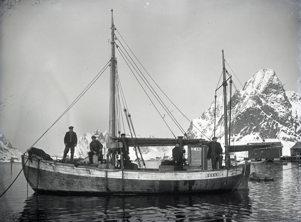 Fem mann på dekk med fjell i bakgrunnen - Fiskeskøyten 'Duen'.