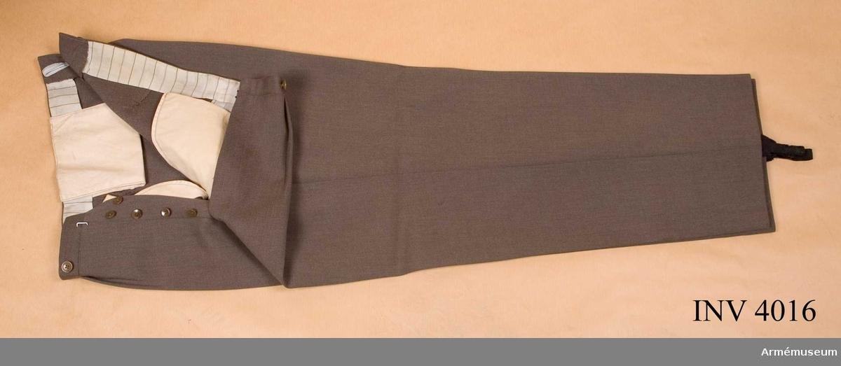 Storlek: D 50. Byxor i grbrgr kamgarnsdiagonal använda till  vapenrock m/1952. Nedtill försedda med knappar och resår,  svart, för att hålla byxan sträckt. Byxan är jylfknäppt, har veck i midjan och litet sprund på de höga bakstyckena. Knappar för hängslen. Byxvidd nedtill: 54 cm.