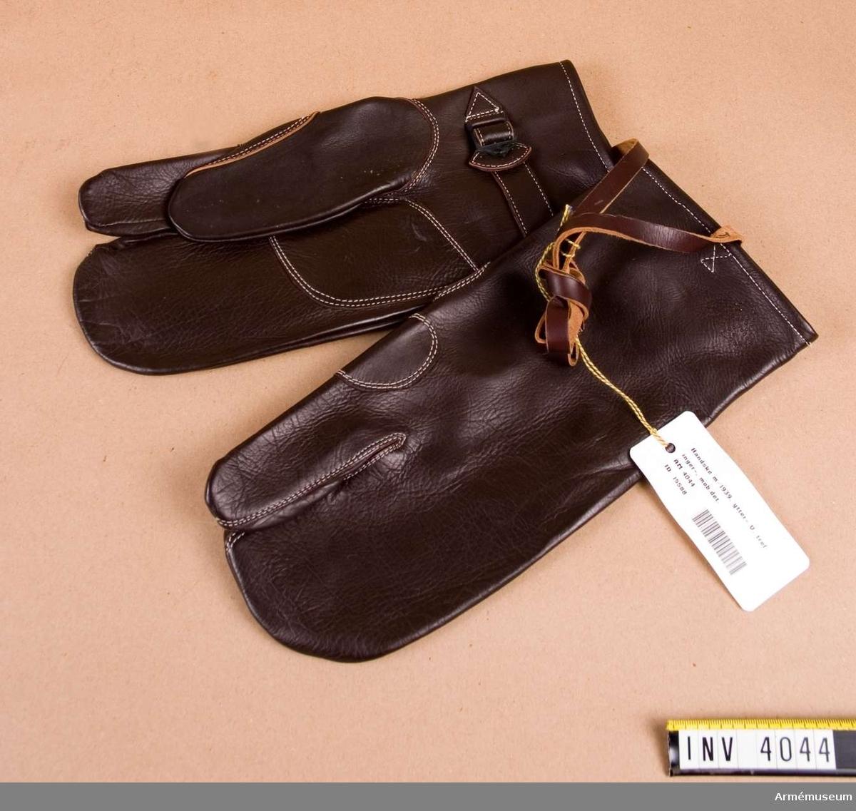 Vänster trefingers ytterhandske till uniform.Trefingers ytterhandske för skjutning m/1939. Av mörkt brunt läder med vita stickningar. Tummen och pekfingret har varsitt  handskfinger, de Övriga ett gemensamt. Skinnet har den blanka  sidan utåt, dubbelt laskade sömmar med en skinnförstärkning i  handflatan. Vid handleden finns en spännrem samt en längre rem för fastsättning runt handleden eller underärmen. Ett inpressat  kronmärke finns vid övre framkanten. Har tillhört rustmästare Olle Skoogs mobutrustning vid AM.