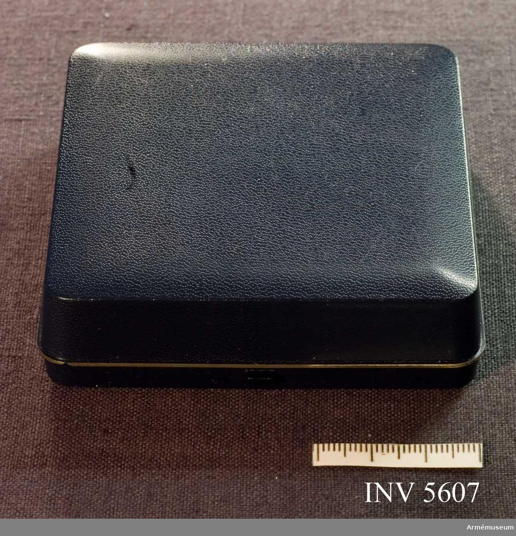 Mörkblå ask tillhörande AM.005607. Av plast i läderimitation, klädd invändigt med sammet och siden. Runt lockets tre sidor löper en smal metallist i gulmetall.
