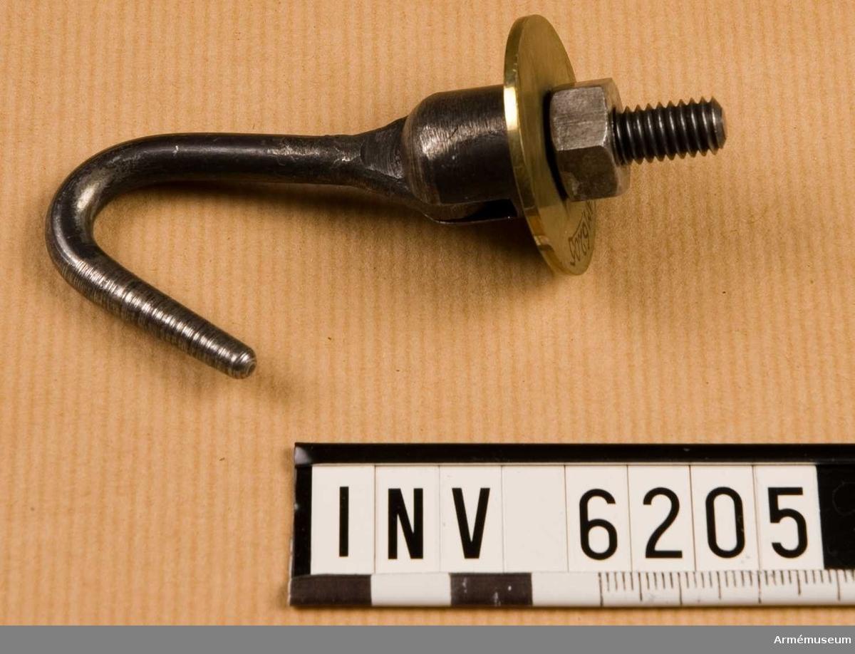 Av järn. En krok, rörlig i sitt fäste. En påträdd bricka av mässing (över skruven) och en påskruvad mutter. Att fastsättas i trumremmens härför avsedda hål.  Samhörande nr är AM.5828-5899, 600-6099, 6200-6212