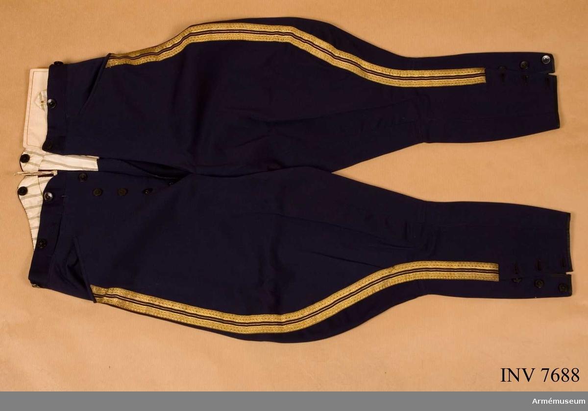 Byxor med vid tillskärning. Tillverkade av mörkblått kläde. Dubbla guldgaloner och emellan dem en guldpassepoil. Storlek B 50. Go 24 jan 1880 nr 46.