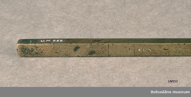 """En fyrkantig avlång solid mässingstav med ingraverad text och måttangivelser på de fyra sidorna för kontroll av rymd och längdmått: CRONO MÅTTSTOCK FÖR HÖGÅHS KYRKA 1748 Å KANNA 1/2 1/4 1/8 1/16 1/32 Å ALN Å SWENSK FOT Å TUNNA 1/4 1/8 1/16 1/32 1/64  I handskriven gåvoförteckning år 1869:  Torstensson, Gurli, ett alnmått sedan år 1749.  Ur handskrivna katalogen 1957-1958: Måttstock, likare av mässing. L. 65,2 cm; olika måttenheter utsatta; """"CRONO MÅTTSTOCK FÖR HÖGÅHS KYRKA 1748"""" Hel."""