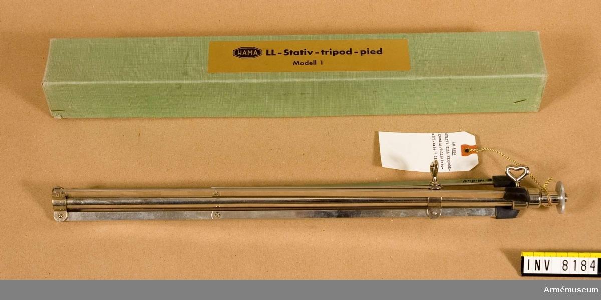 Samhörande nr är AM 8151 - 8199. Belysningsstativet ligger i en märkt papperslåda. På papperslådan sitter en ganska stor, guldfärgad etikett med text. Till vänster på den stora etiketten sitter en liten etikett som det står HAMA på. Efter den lilla etiketten står det LL - stativ - tripod - pied - modell 1.Sista i låda 3. Tillhör fotomaterielsats 7.