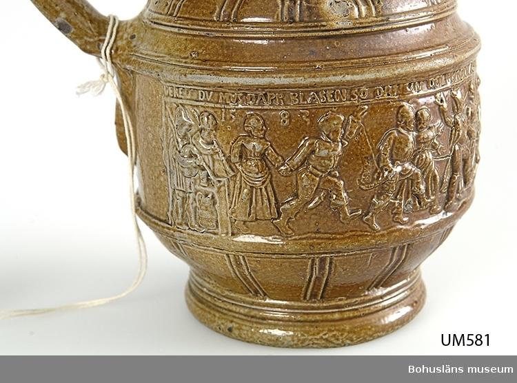 """Föremålet visas i basutställningen Uddevalla genom tiderna, Bohusläns museum, Uddevalla.  Högreståndskeramik funnen i Uddevallatrakten, tyskt importgods, 1500-tal. Mynningens diameter är 5,7 cm, bottendiametern är 8,0 cm. Krus med handtag tillverkat av brunt saltglaserat stengods. En figurscen i högrelief med överliggande textremsa runt livet, ett dekorband i liknande relief runt halsen. I figurscenen finns årtalet """"1583"""". I övrigt olika smala och breda ristade linjer som dekor.  * G:17 i 1869 års tryckta museikatalog.  Ur Nationalencyklopedin, NE.se: Raerenstengods eller Rhenlänskt stengods: Rhenländskt stengods, stengods framställt under medeltid och renässans i Köln med Frechen och Raeren, Siegburg samt under 1600- och 1700-talen Höhr och Grenzhausen i Westerwald. De rhenska krukmakarna introducerade stengodset och saltglasyren i Europa. Tillverkningen av kannor, krus, flaskor och bägare i brunt (Kölnområdet), blågrått eller vitt (Siegburg) hade en stark nationell prägel och innefattade även nyskapelser som bartmannkannan och den för Siegburg karakteristiska schnellen. De skarpskurna reliefdekorerna återger porträttmedaljonger av samtida furstar, bibliska scener, friser med dansande bönder, arabesker m.m. efter förlagor av Aldegrever och andra Kleinmeister. En betydande export ägde rum till Nederländerna, Storbritannien och Skandinavien. Nytillverkning förekommer sedan 1800-talet med ölrestauranger som främsta avnämare.   Uppgifter från tysk väninna till syster Hildegard, Uddevalla, 1990-talet: Raeren är en gammal stad i provinsen Liège i nuvarande Belgien nära gränsen mot Tyskland. Området hörde till Flandern på 1500 - 1600-talen.  Jan Emens Mennicken var den mest framstående keramikern i en krukmakarfamilj, verksam runt 1575, vilket räknas som höjdpunkten i tillverkningen av Raerenstengods. Släkten finns fortfarande kvar.  En samling med föremål från tillverkningen finns på slottet Le Château-Musée.   Litt.: J. Fleming och H. Honour, """"Lexikon för konsthantverk"""""""