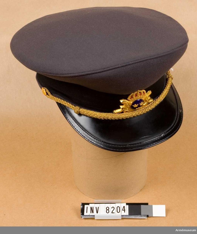 Tillverkad av stålgrått tyg med mösskärm av svartlackerat läder, har stålgrått mössband kring stommen och två små knappar av Försvarets intendenturkårs modell 1880 mindre modellen. Mitt fram mössmärke m/1960 med för officerare blåemaljerad  knapp m/1865. Styvnaden i mössan får ej avlägsnas.Intendentkåren är en för försvaret gemensam personalkår, bildad 1969-1974 av personal som succesivt överfördes från intendenturkåren, fälttygkåren och viss personal från marinen och flygvapnet.Tillverkad av Svenska Epiperings aktiebolaget, Sibyllegatan 31, Stockholm. Firman grundad 1905.Storlek 57. Gott skick 211.