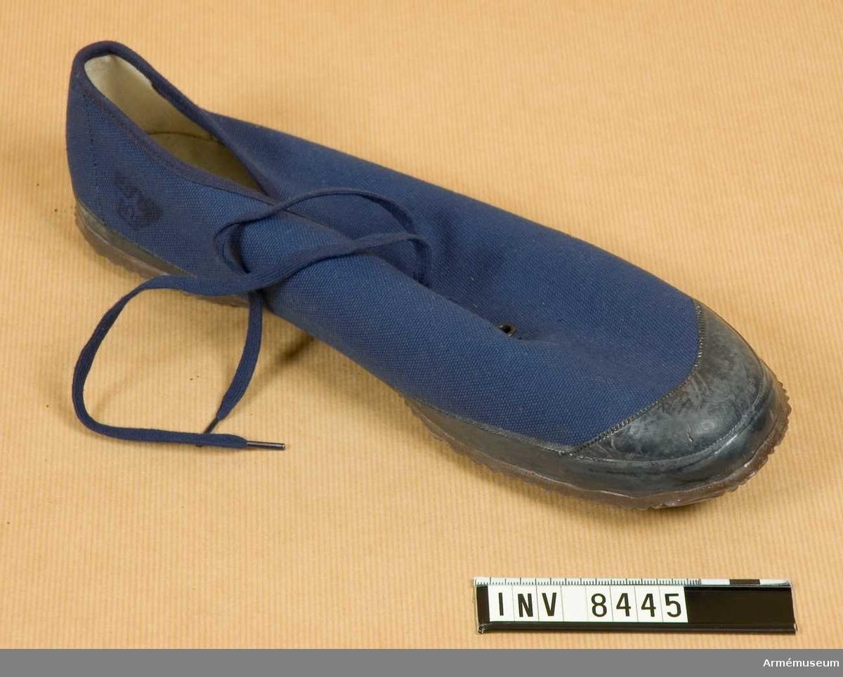Blå med gummisula märkt TRETORN MADE IN SWEDEN 44. Storlek 44. Skodonet snörs genom tio i par, Öljetterade hål med ett blått skosnöre av textil. Skodonet har en svart gummihätta vid tårna.