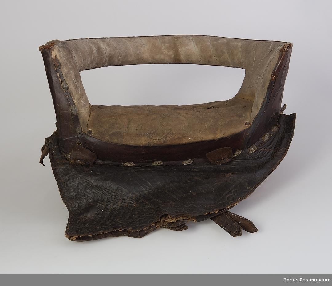 """Tvärsadel av trästomme med ljus vadderad (matelassérad) läderdyna. Lädret är kantat med läderremsor samt dekorativt utformade blyknappar. Dynan, ryggstödet och främre delen har ett sytt mönster med  kedjestygn. Armstöd med vadderad insida med vertikalt sydda kedjestygn. Utsidan är klädd präglat med läder. Baktill är """"AND 1795"""" inskrivet i en """"medaljong"""". Armstödets utsida är målat med tvärställda ränder. Dubbla sidostycken med präglade ränder samt vågformad dekor ytterst. Sömmarna upptill vid dynan har läderremsor fastspikade ovanpå med blyknappar (se ovan). Smidda ringar av järn att fästa stigbygeln i. Läderremmar att spänna sadeln med. Putor av naturfärgad väv med läderkanter och stoppning av halm. Den är rejält skadedjursangripen och ligger löst intill. Trästommen är defekt. Mushål framtill i dynan. Stigbygel saknas.  Litt.; Ur årsboken """"Kulturen 1956"""", Brudsadel 1900, s. 42-43.  Ur handskrivna katalogen 1957-1958: Damsadel L. 58; Br. c:a 50 cm. """"AND 1795""""; dyna och ryggstöd klätt m. ljust skinn; ovala blyknappar (ljutformar t. dylika finns i muséet) lädret arbetat läderplastik? Stoppn. på undersid. trasig. Musbo i dynan.  Lappkatalog: 40"""