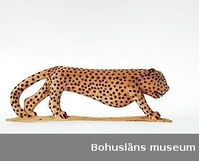 """Text till webbutställning """"Från när och fjärran"""" presenterad på Bohusläns museums hemsida år 2009 - 2013: Träskulptur från Sydafrika, en leopard, täljd och svärtad; längd 41 cm.  Skulpturen ingår i en samling av träföremål föreställande afrikanska djur och människor, de flesta karikerade kolonisatörer. Samlingen skänktes till Uddevalla museum år 1927 av ingenjören Ernst Nomell, Kimberley, Sydafrika.  Uppgifter om givaren Ernst William Nomell föddes i Uddevalla år 1861 som ett av tio barn till handlanden Johan August Nomell och hans hustru Elise Kullgren. Som ung gav han sig ut i världen som lättmatros.  I Sydafrika fick Ernst Nomell kontakt med en man som var engagerad i landets gruvnäring. Det var politikern, finansmannen och imperiebyggaren Cecil Rhodes, en man av brittisk härkomst. Nomell vann dennes förtroende, och han kom att bosätta sig i gruvstaden Kimberley, där Cecil Rhodes år 1888 medverkat i grundandet av diamantbolaget De Beer.  Den forne Uddevallabon kom att arbeta vid bolaget under många år.  Ernst Nomell var mån om att skicka gåvor till hemstadens museum.  Kontinent: Afrika Ur handskrivna katalogen 1957-1958: Träskulptur; leopard. L. 41 cm. H. 14 cm. på språng; prickarna stämplade m. ngt. brännjärn . Hel. Infödingsarbete, Sydafrika.  Lappkatalog: 9 Leopard på träplatta täljd ur ett stycke av ett ljust gulbeige träslag.  Ernst William Nomell var ett av tio barn son till grosshandlarparet Johan August Nomell  och Elise, f. Kullgren i Uddevalla.  Han arbetade som ingeniör vid diamantbolaget De Beer i Kimberley."""