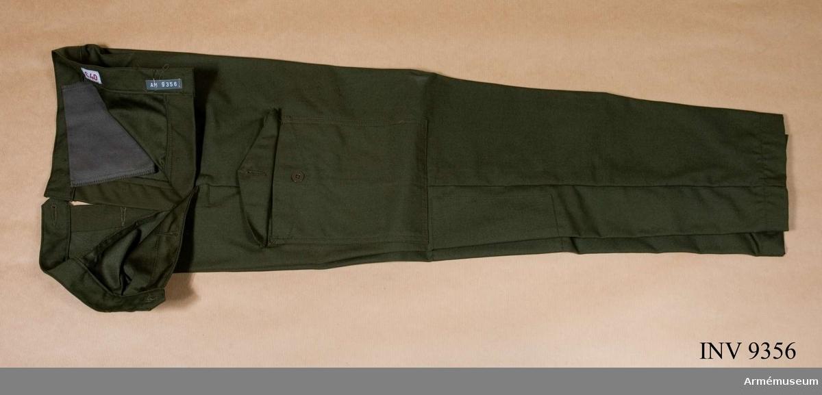 Fältbyxor m/1970 kv.Tillverkad av olivgrön varpsatin - 50 % polyester och 50 % kammad bomull. Försedda med två benfickor med spetsfasonerade ficklock knäppta med en polyamidknapp. En bakficka placerad på höger bakbyxa försedd med knapphålsslejf och knapp av polyamid. I varje sidsöm ett c:a 20 cm långt sprund med knapp och  knapphål placerat mitt på. På linningens yttersida vid varje sidsöm två polyamidknappar för reglering av midjevidden. Avsmalnande benvidd nedtill. På insidan av varje byxben nedtill två polyamidknappar på vilka knäpps hålfotshällor av svart resår. En hängare fastsydd i midjebandet mitt bak på byxornas insida. Märkning: På midjebandets insida vänster bakbyxa vävd vävd storleksetikett: C 40. På baksidans fickpåse stämpel Tre kronor 1977 OLJON (firmanamnet för tillverkaren Olsson & Johnsson (sic), Malung). Gåva från FMV i Solna.