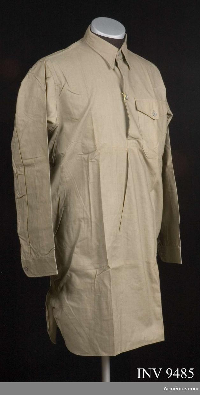 Skjorta m/1939, Livregementets husarer K 3. Gråbrungrön skjorta i bomull med fast krage och linning vid ärmen, en ficka, vänster. Knäpps i sprund med två kompositionsknappar, samt en dito på ficklocket. Märket på kragens insida: Engers 38 20 K 3.Storlek 38.
