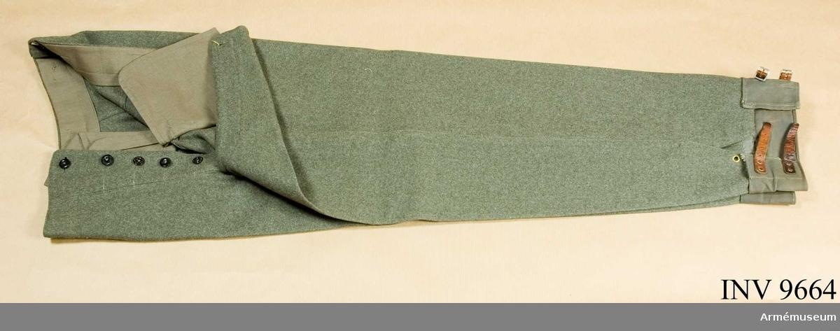 Långbyxor i gråbrungrön yllediagonal. Jylfknäppning med fem knappar av olika modell. I linningen, som ser ut att vara påsydd senare, finns sju beige knappar. Isydda sprund i  sidosömmarna bakom de snedställda fickorna. En bakficka i höger sida vars fickpåse har påstämplat: Örnkläder. Dubbla hällor av grått resårband påsydda i byxbenens nederkanter. Gåva från kapten Hilding Lekman i Spånga.