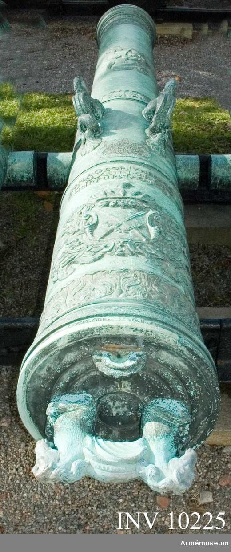 """Grupp A I.  Krigsbyte från den invid Dünamünde belägna skansen Neumünde, som den 11 dec 1701 erövrades av svenskarna. Följande inskrift syftar härpå: MED GUDS HIELP AF K CARL XII TAGIT MEDH  FESTNINGEN NEUMUNDE 11 DECEMB 1701.  Kanonen utmärker sig f.ö. genom sin högst praktfulla utstyrsel och fullkomlighet, vad tillverkningen beträffar. Gjuten under Johan Georg III:s regering.  På långa fältet: bilden av en gosse ridande på en delfin.  På kammarstycket: hertigens av Sachsen hjärtvapen och därovan inskrift """"JOHA. GEOR. III HERZOG / ZU SAXEN.J.C.B. E.U.W / CHURFURST Ao 1691, No 3"""". På kammarbandet """"W.C.V. CLENGEL GEN. WM.V. ZEVG  OBR. G.M.ANDREAS HEROLD I. DR."""" Mynningsplanet märkt """"21"""". Höger tapp """"X (?) X - XI VII""""."""