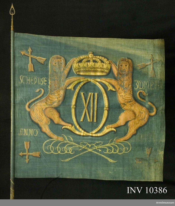 Grupp B I. Fanduk av blå lärft, hopsydd av två våder, med målade emblem: Karl XII:s spegelmonogram av dubbelt C med XII därinom under sluten kunglig krona, hållet av två gulbruna lejon, som står på två korslagda och med bandrosett hopknutna palmkvistar i grönt. I vardera hörnet Dalarnas sköldemärke, två korslagda pilar inom korslagda palmkvistar, allt i gulbrunt och brunt.  Namnchiffret och kronan i guld, övriga emblem i gulbrunt och brunt. Fastspikad med blått linneband och mässingsspikar. Bandet lindat sex varv runt stången nedom duken. Stång av grönblåmålad furu. Spets av mässing i ett stycke, holken med  profilerade vulster. Bladet med Carl XII:s spegelmonogram i  genombrutet arbete, dess längd 29 cm.