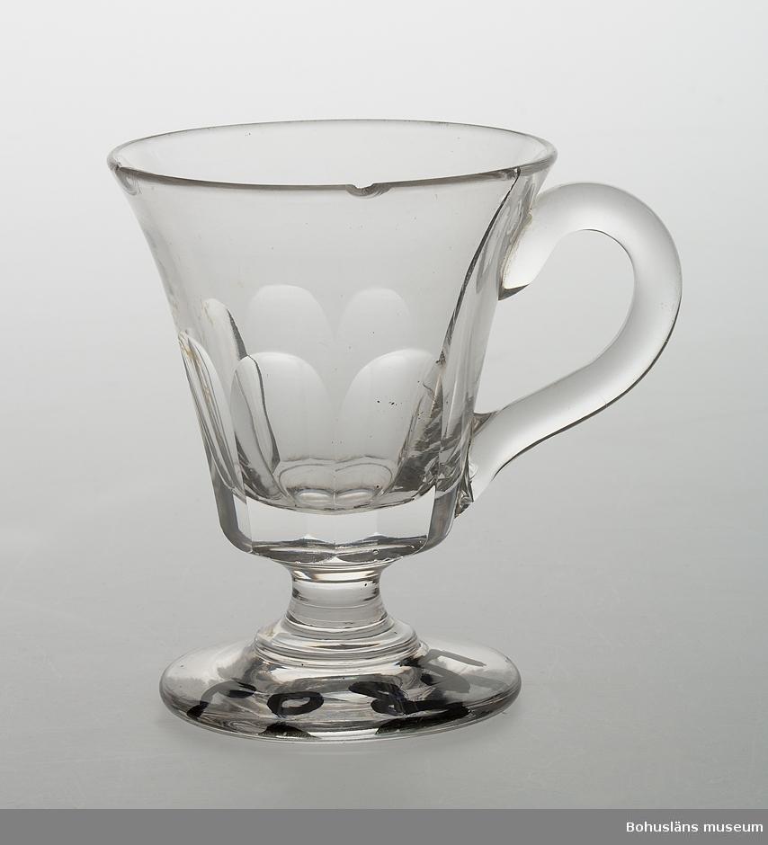 Ur handskrivna katalogen 1957-1958: Litet glas på fot med öra Mynningsdiamet.: 6,4 cm. Fotens diamet.: 5,3 cm. H.: c:a 8,1 cm. Vitt glas, slipat. Spräckt.