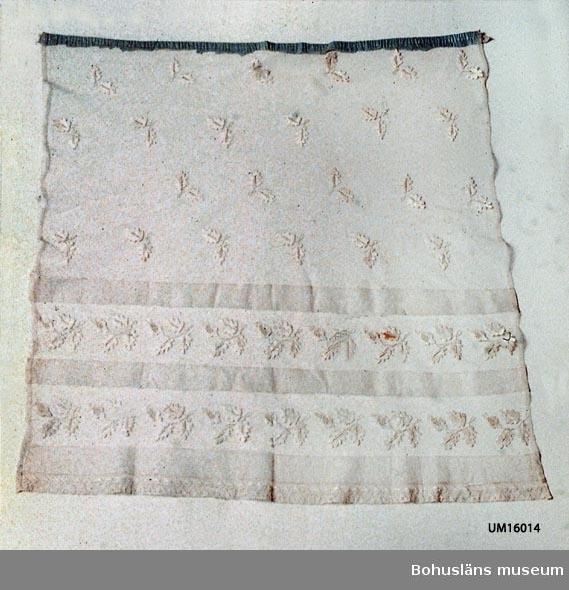 Färg: vit med vita broderade eklöv i linnegarn över hela manteln. Nedtill två bårder om vardera 200 mm med större löv.Tre sydda tvärveck Spets i nederkanten. På tyllet finns ett ljusblått smal tyg av cellulosafiber upptill på manteln.Spår av att den varit rynkad. Dopklänningen har tillhört Charlotta Söderbom och sänktes av henne till Hemslöjdsföreningen i oktober 1915 Strömstad genom B.Kleberg. Denna mantel broderades av fröken Marie Liedberg 1849 och användes av alla syskonen Söderbom dessutom många många andra Strömstadsbarn.  För ytterligare uppgifter om givaren se UM 16001.  Litt.: Wintzell, Inga, Så var barnen klädda, Från kolt till täckjacka, Natur och kultur, Stockholm 1972, s. 41-59, Dopdräkten.