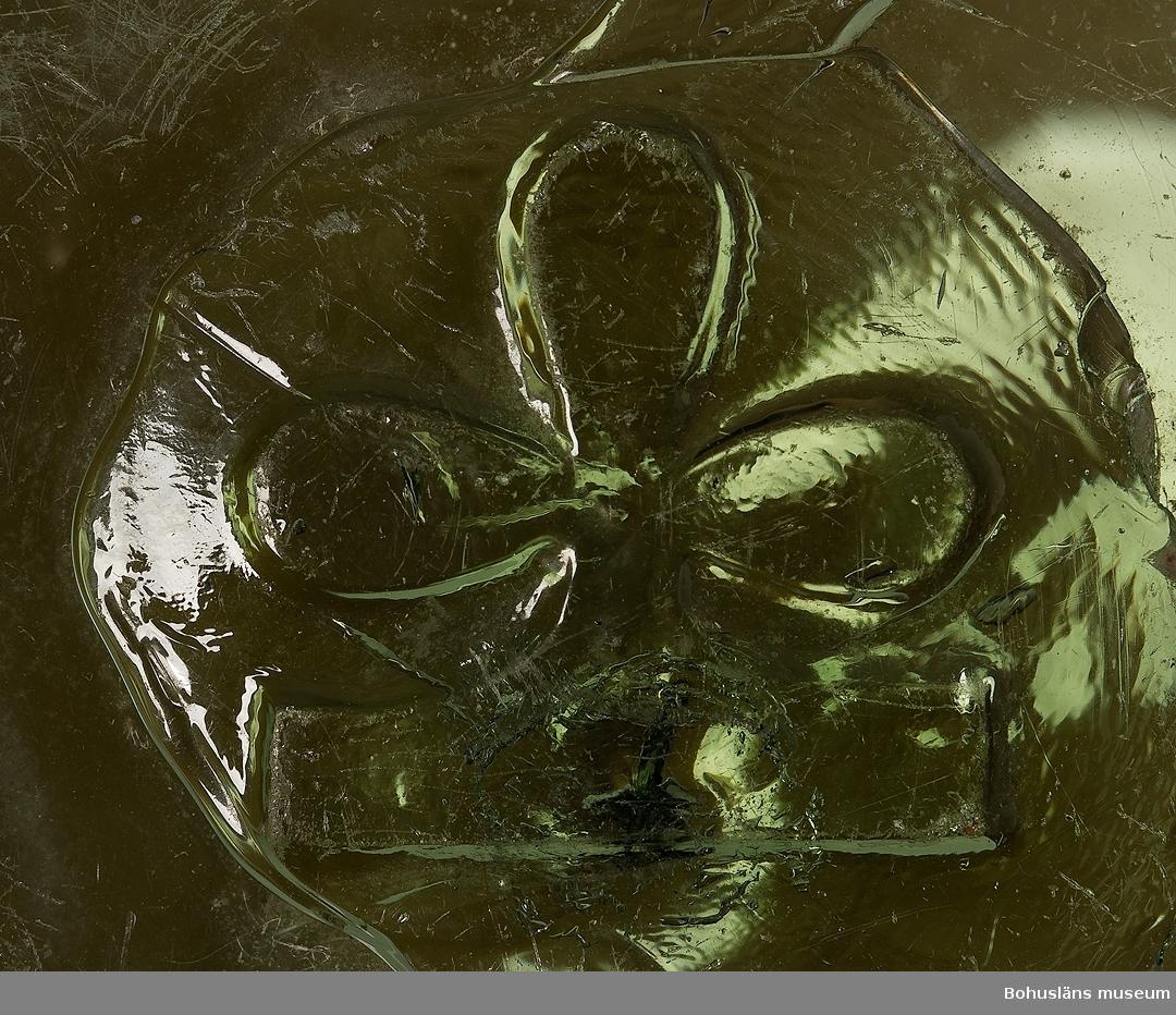 Ljusgrön kula. I glasmassan i proppen som satts i puntelhålet efter blåsningen är en treklöver inpressad i relief.