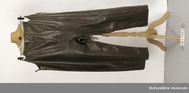 Arbetskläder vid fiske. Hängslebyxor att dra över annan klädsel som skydd mot väta. Gröna. Går upp över bröst och rygg. I överkanten är det knappar att fästa hängslen i. På knapparna står det Grundéns. Tre knappar saknas. Hängslen saknas. Hål på ena knät.  Ingår i redskapsbestånd ur sjöbod från Hällsö, Havstenssund, Tanum socken. Se UM017521. Historik om Grundéns se UM025938