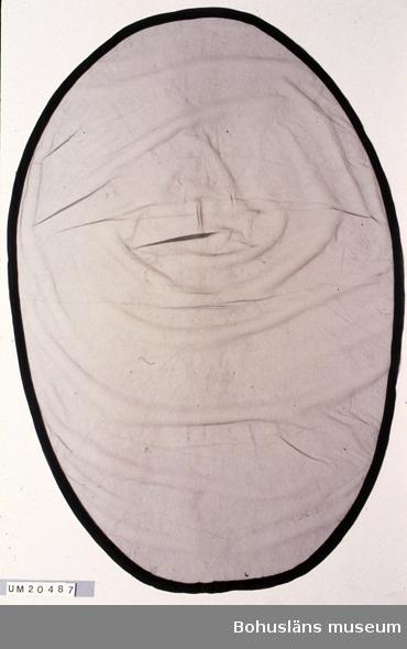 Oval svart slöja av tyll. Med en 2,7 cm bred kant av kräpp ytterst, fastsydd med symaskin. Troligen använd sent 1930-tal fram till tidigt 1950-tal. (Jämför med UM020486.) Har tillhört Vilma Börjesson (1906-1986), från Lysekil, gift med Kjell Börjesson (1905-1965). Innehade Kjells Herrkläder i Lysekil. Personuppgifter om givaren se UM020411. Några mycket små hål i tyllen, troligen från när slöjan fästs på sorghatt.  Omkatalogiserat 1997-05-28 VBT