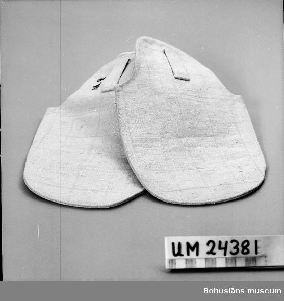 """594 Landskap BOHUSLÄN  2 st """"påsar"""". De saknar tummar. Dubbelt tyg. En hälla på varje sida, i vilka ett bälte kunde kopplas. Oanvända(?). Svart tryck på varje vante, text: """"M2"""" (?). När patienten ville riva och klösa sig själv eller andra eller inventarier användes vantarna."""