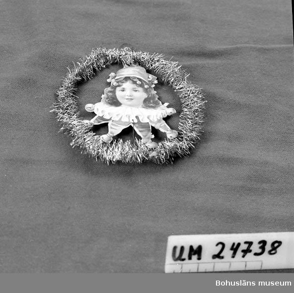 471 Tillverkningstid 1920-40 ? 594 Landskap BOHUSLÄN   Metalltråd med tunna metallpappersremsor/trådar i en krans. I kransens mitt ett bokmärke - ett flickansikte med Harelquinkläder. Givarens mamma född Augustsson (1898 - 1978).