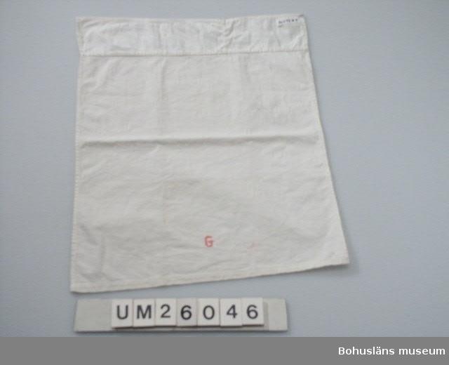 """Vit bomull. Förlängt med 6 cm långt stycke. Prytt med """"G"""" för Gunda i rosa korsstygn. Tillhör bäddutrustning UM0260444 - UM026048 till dockvagn UM026043. Släkt- och personuppgifter se UM026024"""