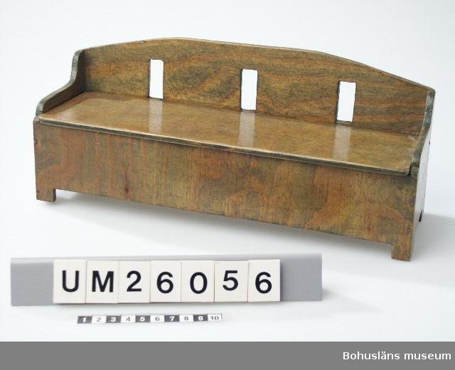 Möbel till dockskåp. Grönbetsad docksoffa, svängt, genombrutet ryggstöd. Morbrodern Anders Jacobsson tillverkade en likadan möbel till Gundas syster Ulla, men rödbetsad.   Se UM026053 Släkt- och personuppgifter se UM026024