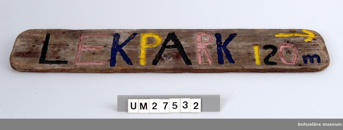 Vägskylt tillverkad av elev vid Åstols skola, Tjörns kommun. Vägskylt  tillverkad av en bit drivved. På framsidan inhuggna texten LEKPARK 120  m, målat i rgrönt, rosa. blått och gult samt en pil som pekar åt höger.  Borrhål för skruvar.  Föremålet visades i utställningen Moderna skärgårdsbor på Bohusläns museum 2002. Utställningstext: Vägskyltar Nio skyltar som vägvisare på Åstol.  Från affären till rökeriet är det 375 meter och från skolan till badplatsen är det 200 meter. Skyltarna berättar om en liten ö med många mötesplatser. Här finns affär, bibliotek och skola - restaurang, lekpark och flera församlingar. En tätbebyggd ö omgiven av havet, med skolan i centrum - så viktig för barnfamiljerna och åretruntboendet. Skyltarna är gjorda av elever i årkurs 4 - 6 på Åstols skola.  Skylten ingår i insamlingen i projektet Moderna skärgårdsbor, UM27511 - UM27595 och kommer från Åstol.   För övrigt material från Åstol, se UM27524-UM27538 och UM27566-UM27594; UM27524 Tjörn Runt-teckning UM27525- Vägskyltar, 9 st UM27533 UM27534:1-2 Eternitplattor, 2 vita refflade  UM27535 Eternitplatta, 1 vitmålad slät UM27536:1-2 Eternitplatta, 2 gröna UM27537 Cykelkärra UM27538 Matjordsäck, 2 st (omärkt) UM27566- 28 barnteckningar över Åstol, indiv. inv.nr. UM27593 UM27594 Skylt frikyrkan med gudstjänstaffisch Arkivet 9 uppsatser från skolbarnen i samband med teckningarna.  För information om projektet Moderna Skärgårdsbor, se UM27511.  Litt: Sjöholm, Carina. Moderna skärgårdsbor i gammal kultur. Skrifter utgivna av Bohusläns museum och Bohusläns hembygdsförbund nr 73. Bohusläns museums förlag.  Avsnittet om Åstol s. 17 - 45..