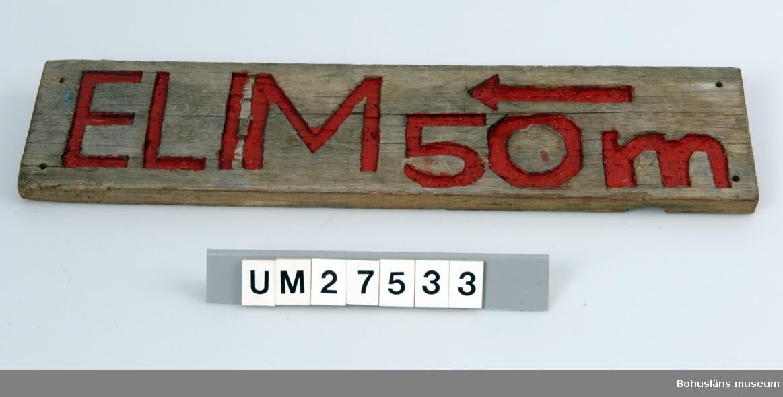 Vägskylt tillverkad av elev vid Åstols skola, Tjörns kommun. Vägskylt  tillverkad av en bit drivved. På framsidan inhuggna texten ELIM 50 m, målat i rött samt en pil som pekar åt vänster.  Borrhål för skruvar.  Föremålet visades i utställningen Moderna skärgårdsbor på Bohusläns museum 2002. Utställningstext: Vägskylta Nio skyltar som vägvisare på Åstol.  Från affären till rökeriet är det 375 meter och från skolan till badplatsen är det 200 meter. Skyltarna berättar om en liten ö med många mötesplatser. Här finns affär, bibliotek och skola - restaurang, lekpark och flera församlingar. En tätbebyggd ö omgiven av havet, med skolan i centrum - så viktig för barnfamiljerna och åretruntboendet. Skyltarna är gjorda av elever i årkurs 4 - 6 på Åstols skola.  Skylten ingår i insamlingen i projektet Moderna skärgårdsbor, UM27511 - UM27595 och kommer från Åstol.   För övrigt material från Åstol, se UM27524-UM27538 och UM27566-UM27594; UM27524 Tjörn Runt-teckning UM27525- Vägskyltar, 9 st UM27533 UM27534:1-2 Eternitplattor, 2 vita refflade  UM27535 Eternitplatta, 1 vitmålad slät UM27536:1-2 Eternitplatta, 2 gröna UM27537 Cykelkärra UM27538 Matjordsäck, 2 st (omärkt) UM27566- 28 barnteckningar över Åstol, indiv. inv.nr. UM27593 UM27594 Skylt frikyrkan med gudstjänstaffisch Arkivet 9 uppsatser från skolbarnen i samband med teckningarna.  För information om projektet Moderna Skärgårdsbor, se UM27511.  Litt: Sjöholm, Carina. Moderna skärgårdsbor i gammal kultur. Skrifter utgivna av Bohusläns museum och Bohusläns hembygdsförbund nr 73. Bohusläns museums förlag.  Avsnittet om Åstol s. 17 - 45..